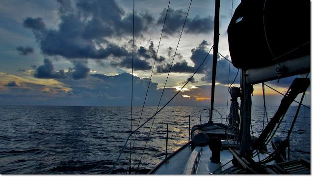 sailing towards an ocean horizon at sunset. Orange and yellow peek through a cloudy sky.