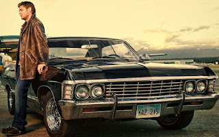 Joshua's brother Jensen Ackles posing for a picture with a classic car