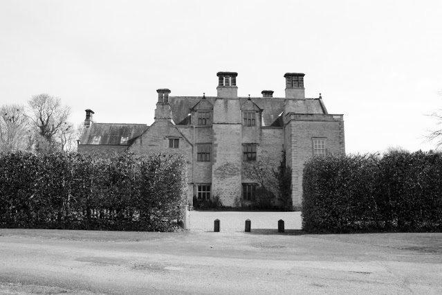 Monochrome photo of Nunnington Hall with large bushes in front and a large gravel courtyard.