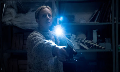 "Detective Muldoon (Andrea Riseborough) shines a flashlight in an empty room after she hears a loud noise in the Sony Pictures remake of ""The Grudge."""