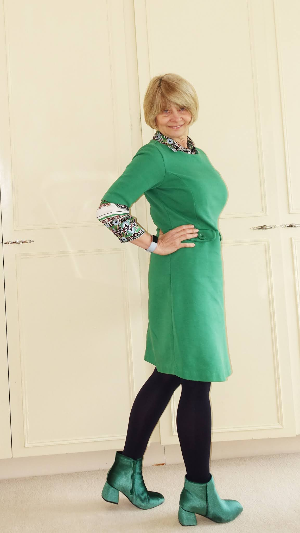 Gail Hanlon from Is This Mutton in a green dress and green velvet ankle boots