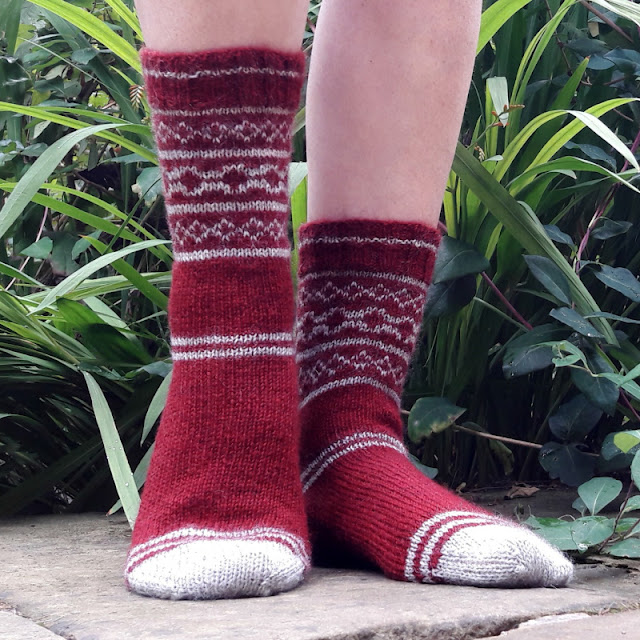 A pair of red and grey colourwork socks being modelled on feet.  The model is standing on a grey stone slab against green leaves