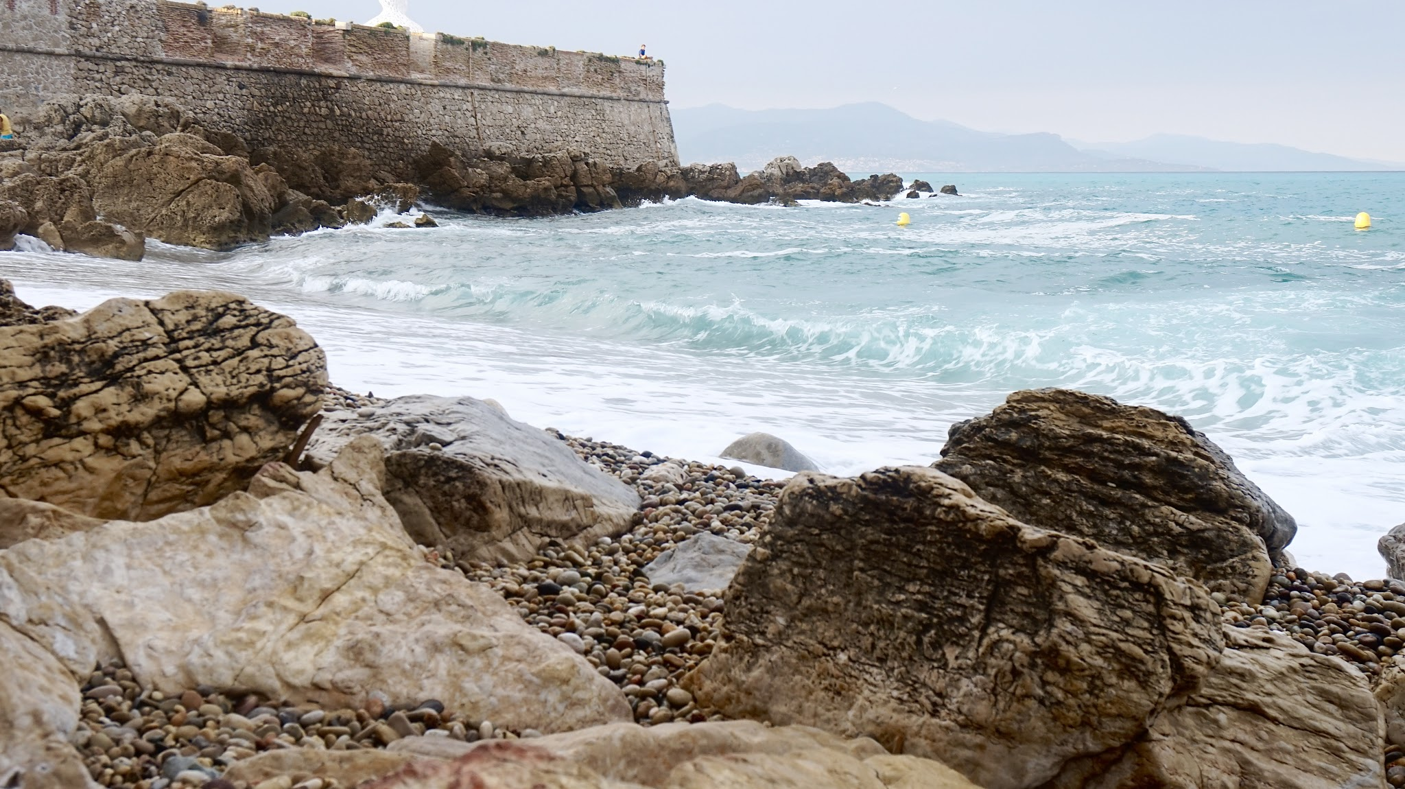 a light blue choppy sea coming into a pebbly beach surrounded by a high stone wall