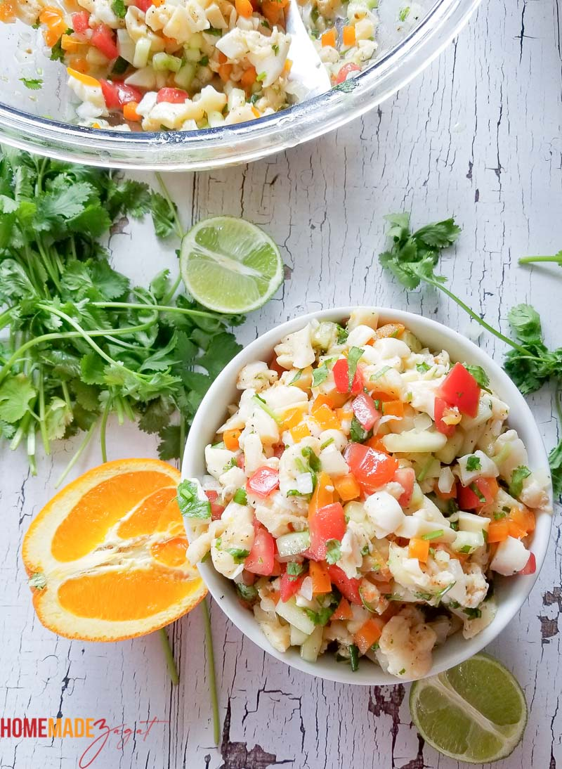 A large bowl of conch salad and a small white serving bowl filled with salad