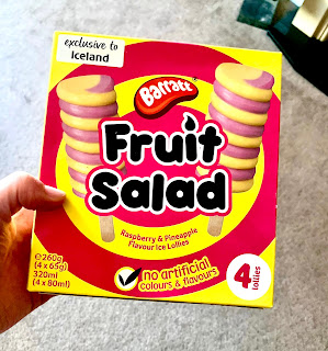 A square yellow and red striped box containing ice lollies with fruit salad ice lollies in black font on a bright background