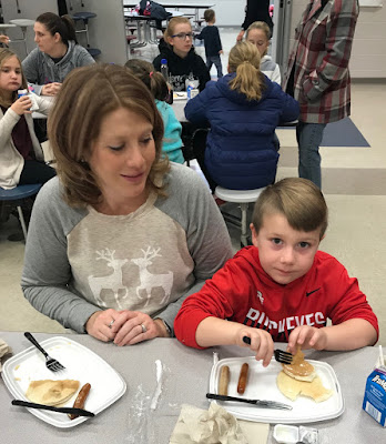 A woman sitting at a table, in a cafeteria, watching a child sitting next to her eat his fluffy pancakes