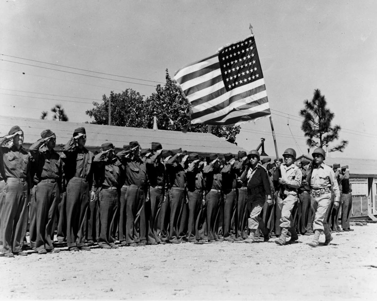 Soldiers of the 442nd salute the flag at Camp Shelby, Mississippi. June, 1943.
