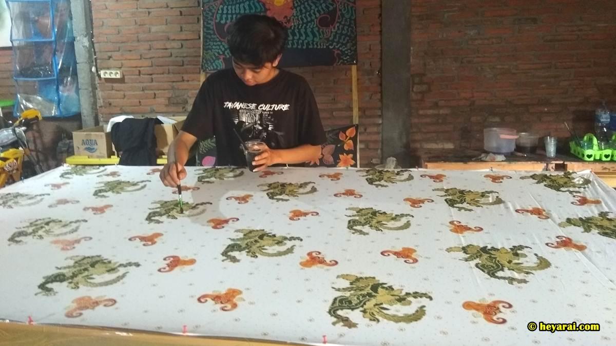 Tio sedang mewarnai kain batik Bantengan