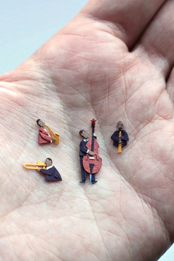 tiny papercut musicians in palm of hand