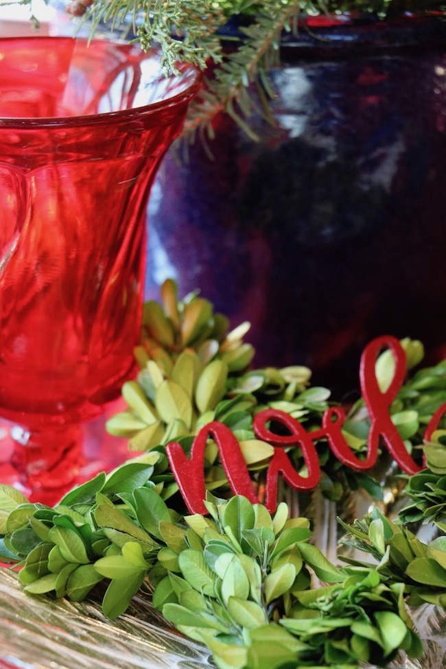 A deep red metal NOEL gives both a traditional red color and message on the Christmas Red and Navy Blue Table Setting