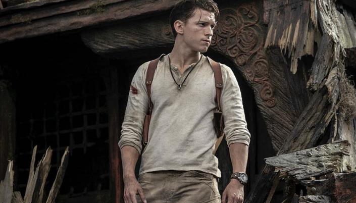 Imagem: o ator Tom Holland interpretando Nathan Drake, numa blusa branca, um relógio em seu pulso e uma mochila nas costas, e por trás, um fundo de madeira com entalhes detalhados, como se fosse um lugar histórico e antigo, porém agora explodido.