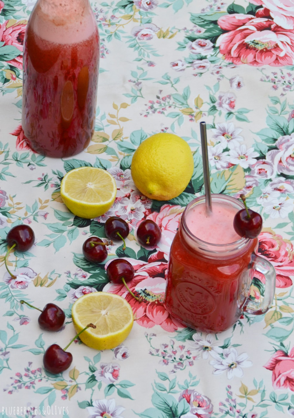 cherry lemonaDE IN Glass jar, cristal bottle full, flowered table cloth over green grass, pieces of lemon and cherries