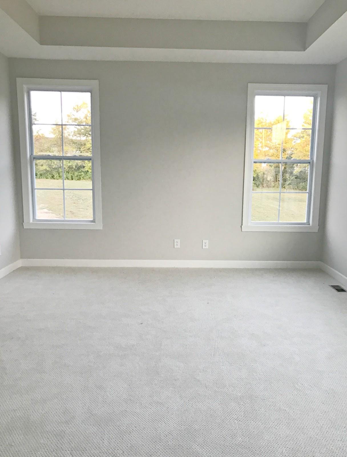 Long master bedroom with bed between windows