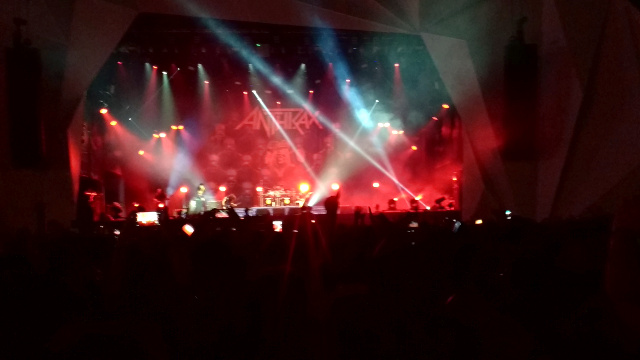 The band Anthrax over a stage with many red lights playing at Rock in Rio.