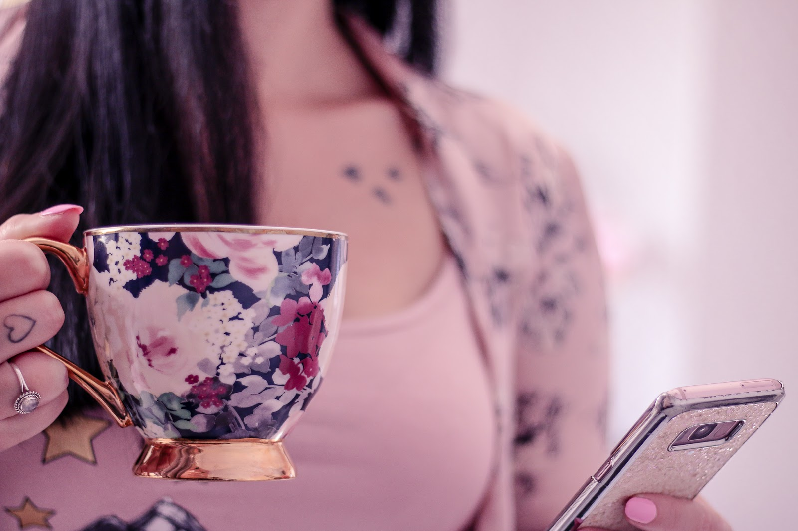 Close up photo of Ofaglasgowgirl holding a flower mug and a samsung s10+ in pink pjs and pink satin robe