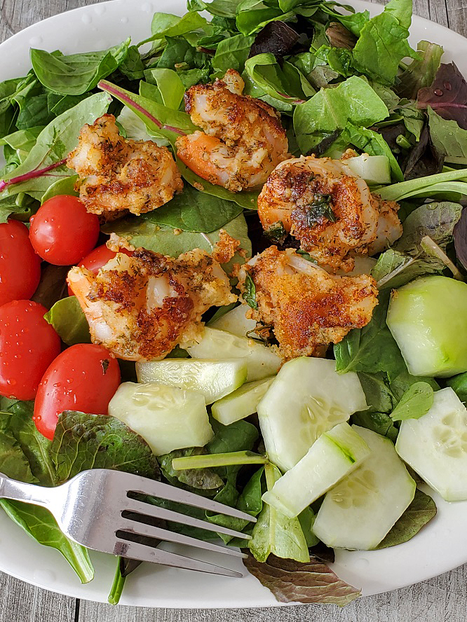 this is cajun shrimp fried on top of  fancy salad greens