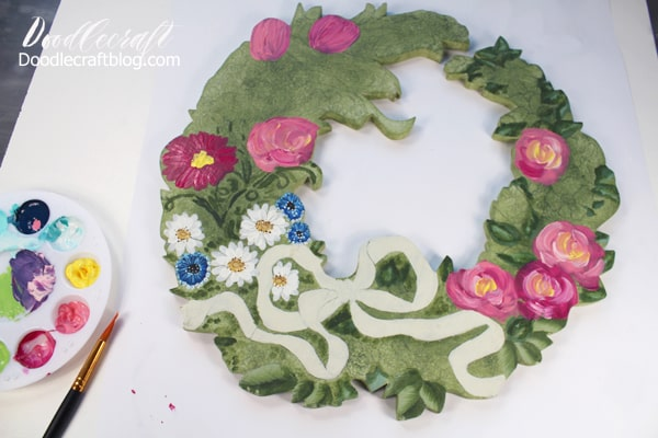 Using acrylic craft paint on a wooden cut out wreath.