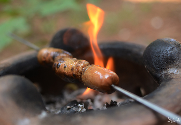 Image of meat sausages being barbecued over an open flame on skewers in a clay oven