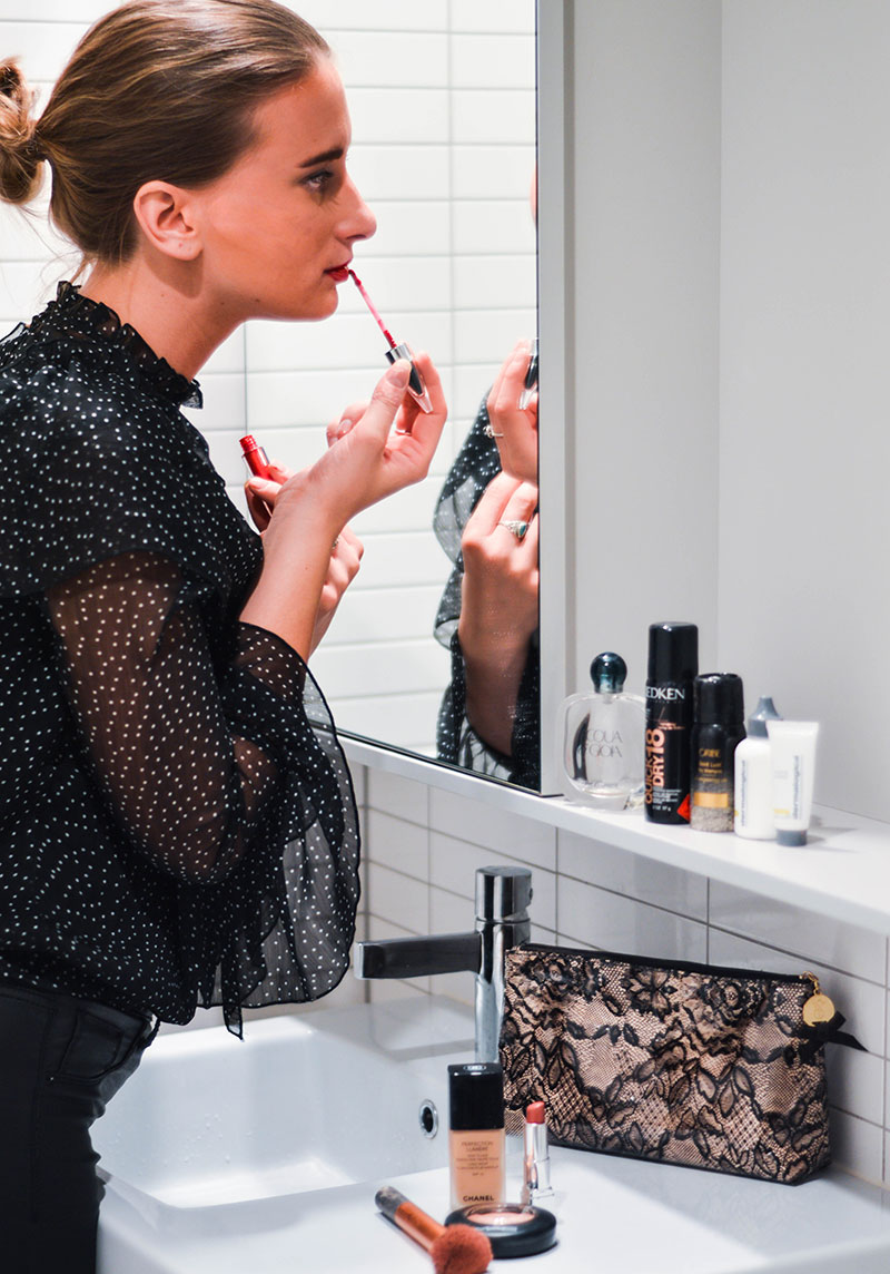 fashion blogger applying red lipstick in hotel mirror in melbourne hotel