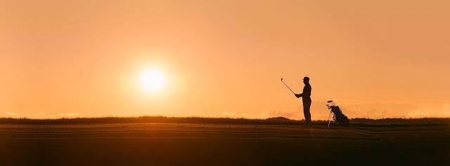 sunset on golf course.Photo by Christoph Keil on Unsplash