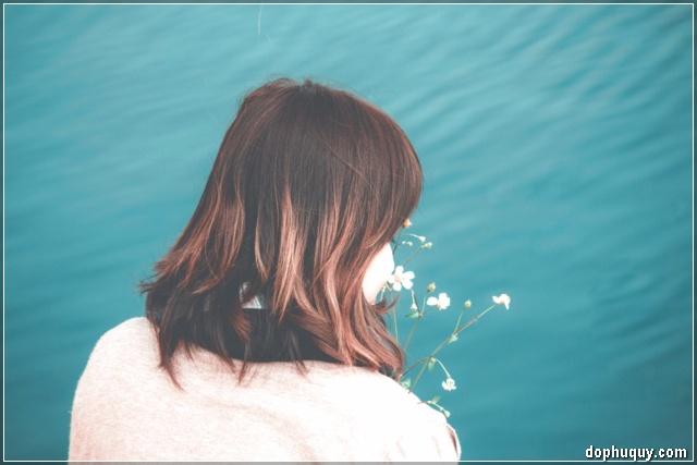 cô gái buồn với nhành hoa dại