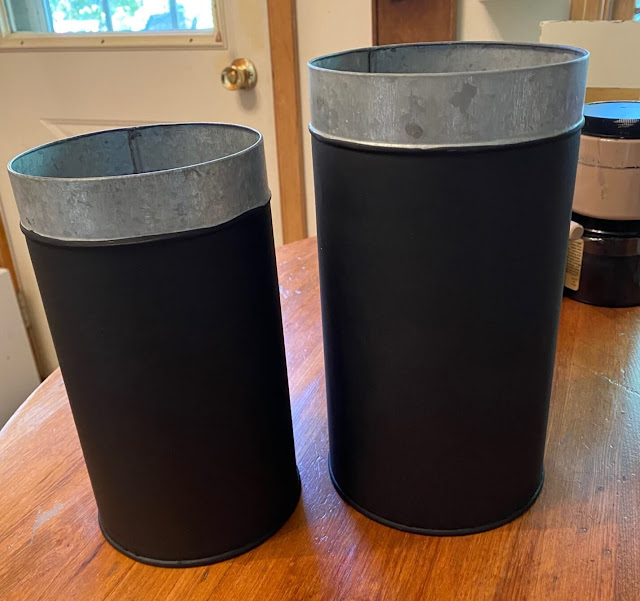 Photo of two galvanized canisters painted black.