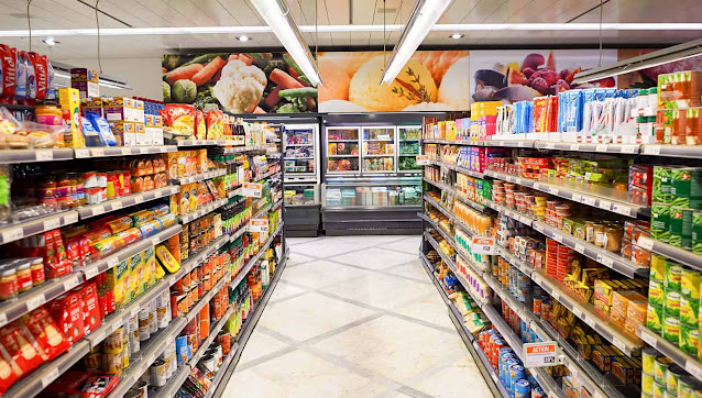 Inside of a supermarket with varieties of items on shelves.