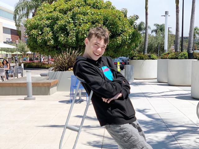 teenage boy leaning on crutches