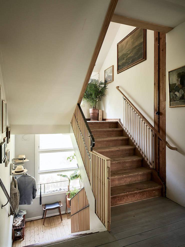 Un ático con una reforma de cocina low cost: escaleras y arrimadero de madera.