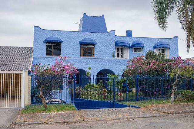 Casa, pintada de azul, com bonito jardim