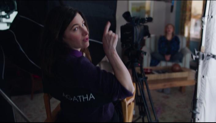 Imagem: Agnes sentada na cadeira do diretor, com uma câmera e um refletor na sua frente, olhando para a câmera e erguendo o dedo aos lábios, enquanto quebra a quarta parede olhando para a câmera.