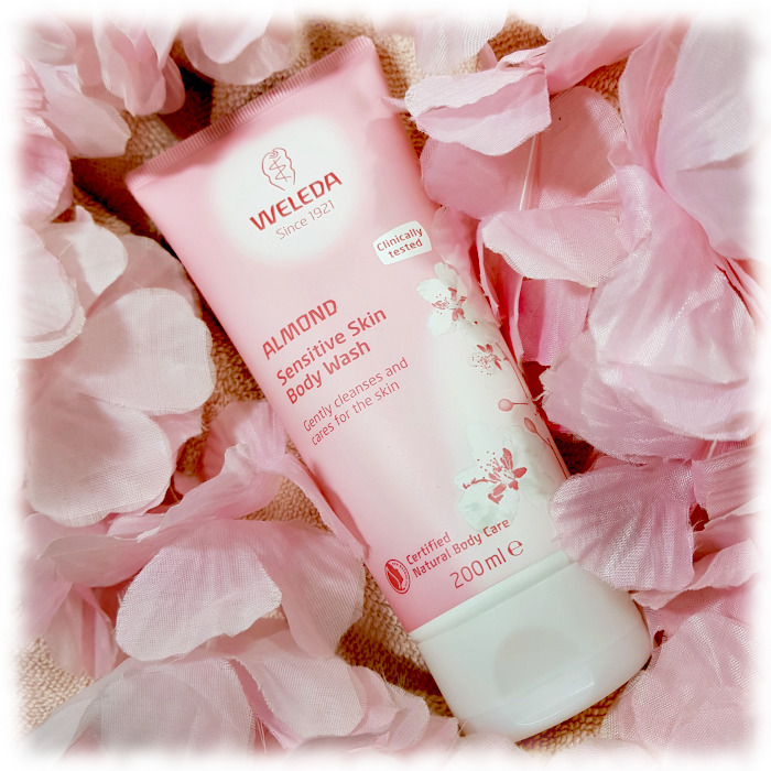 Weleda Almond Sensitive Body wash pictured with pale pink petals