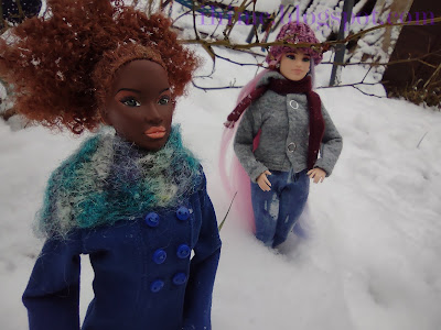 two dolls, on the left Janay in deep blue coat and green wool scarf, on the right Barbie with pink and purple hair in purple wool hat, grey jacket and jeans, both standing in knee-deep snow.