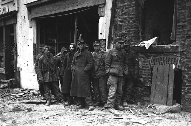 These German soldiers stand in the debris strewn street of Bastogne, Belgium, on January 9, 1945, after they were captured by the U.S. 4th Armored Division which helped break the German siege of the city.