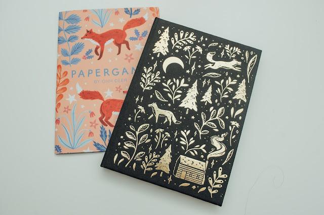 A black hardback notebook with gold foiled floral, leaf and fox illustration