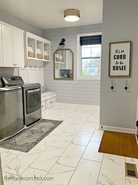 Laundry mud room combo with marble tile white cabinets