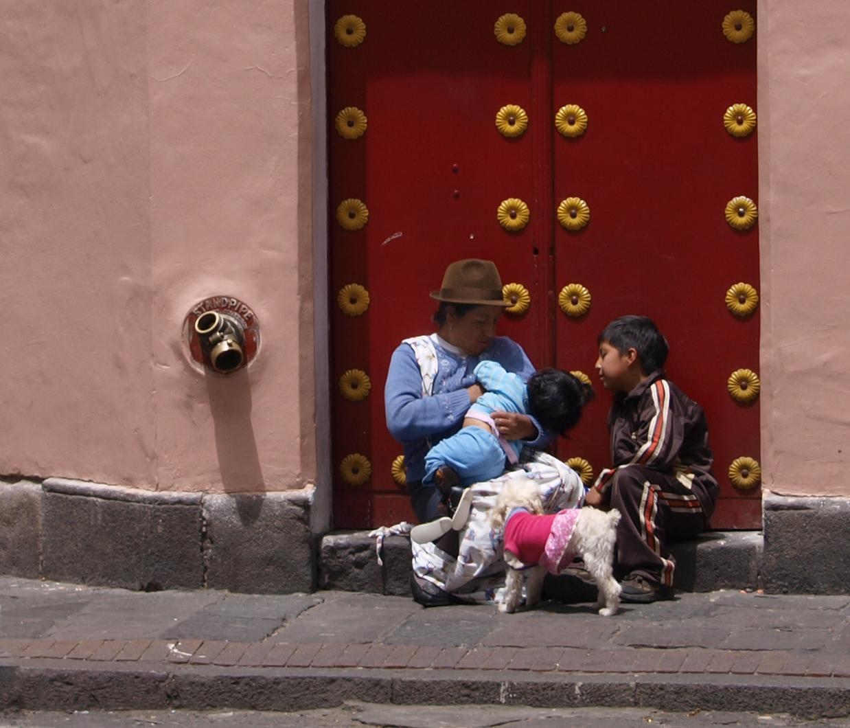 Mãe latina cuidando dos filhos à porta vermelha de um prédio: ilustra a seção a respeito dos textos das linhas de ''Chia Jen / A Família'', um dos 64 hexagramas do I Ching, o Livro das Mutações