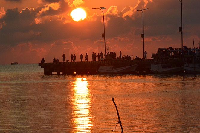 Orang-orang di pelabuhan melihat sunset