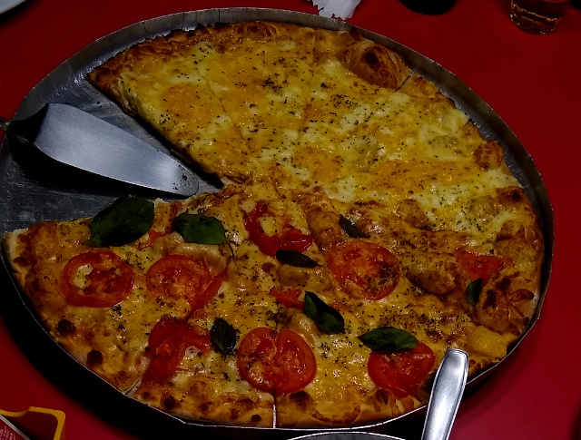 A pizza large pizza divided into Margherita and four cheese.