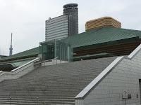 The stairs leading up to the green-roofed Kokugikan sumo hall with the Skytree visible far left