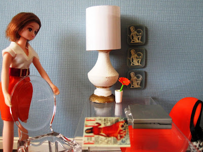 One-twelfth scale modern miniature office scene in shades of light blue and orange, with a dolls pulling out a visitors' chair on one side of the desk.