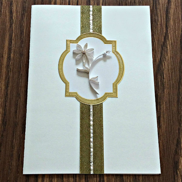 quilled white flower on white rectangular card with gold trim