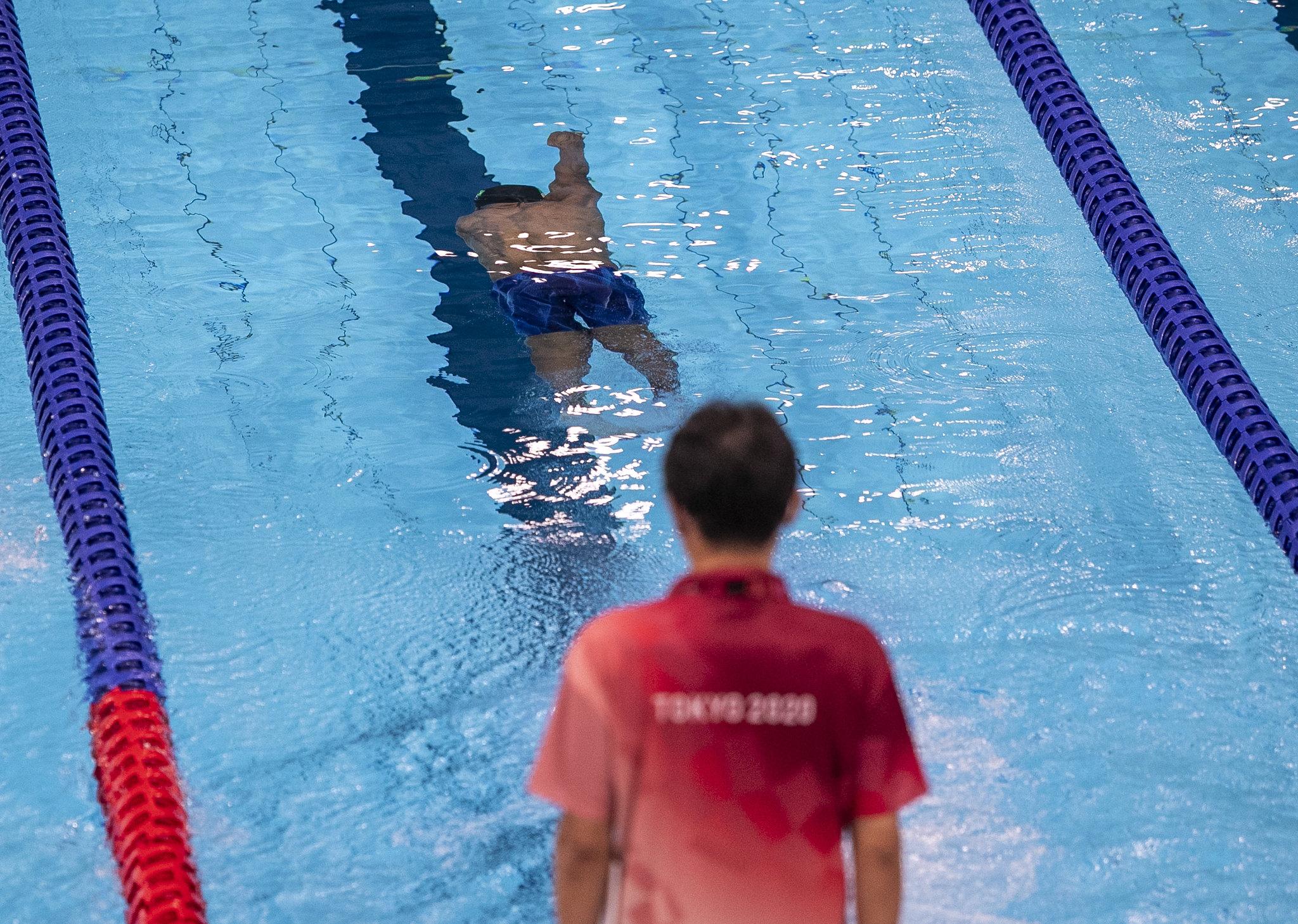 pessoa com camisa vermelha escrita Tóquio 2020 acompanha nadador paralímpico na piscina