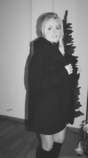 Imagen en blanco y negro de Alejandra Colomera con falda de cuadros mostaza, lazada a juego, jersey negro y abrigo estilo sesentero