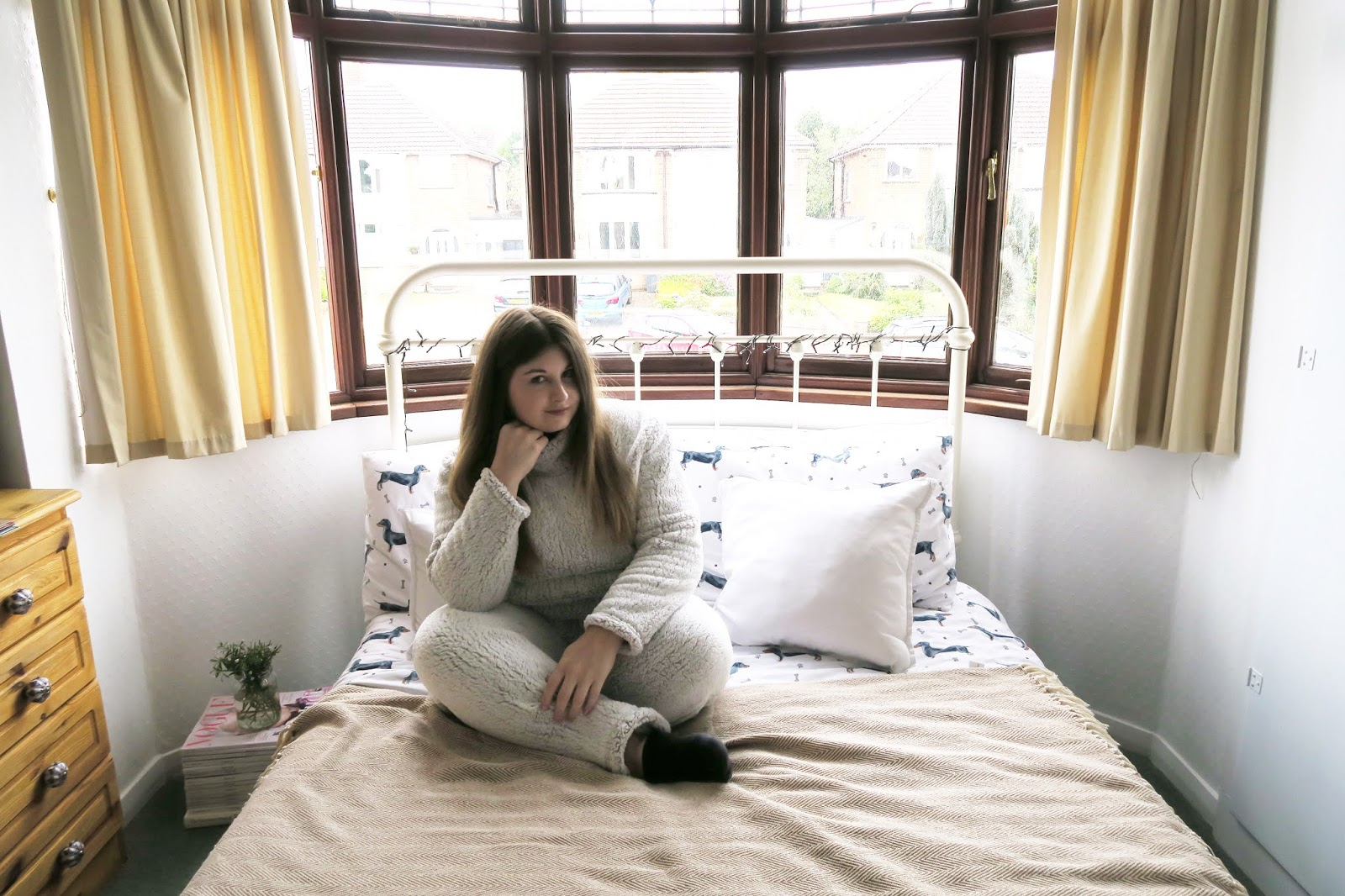 Grace can be seen sitting cross legged on her bed. She is wearing a thick fluffy grey loungewear set