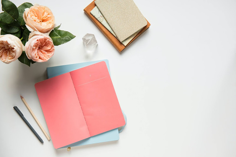 notebook, pen and flowers on white background