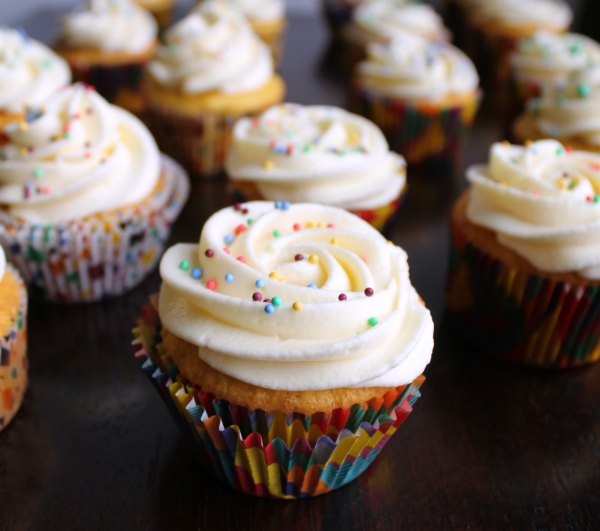 cupcakes with swirls of sweetened condensed milk Russian buttercream frosting and colorful nonpareils