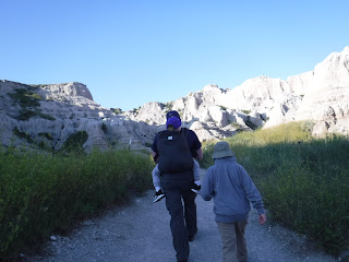a man walks along a trail at Badlands National Park with a boy next to him, and a smaller boy in a carrier on his back