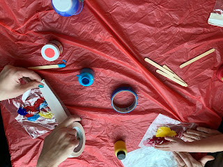 table with finger paints and hands sealing ziplock bags filled with paint