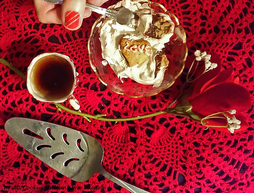 this is a chocolate heart cream pastry filled with chocolate pudding, whipped cream, espresso coffee, a rose and old vintage serving cutter. The photo has the Valentines day piece of heart shaped dessert in a glass bowl  cut up